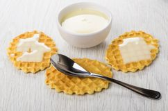 Bowl with sweet condensed milk, milk on wafer cookies, teaspoon. On wooden table Stock Images