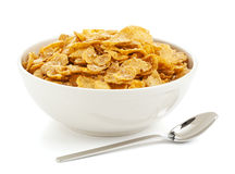 Bowl of sweet corn flakes. Bowl of sugar-coated corn flakes and spoon isolated on white Stock Images