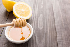 Bowl of sweet honey and lemons on wooden table Royalty Free Stock Photo