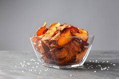 Bowl of sweet potato chips and salt on table. Against grey background royalty free stock photo