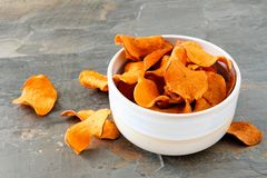 Bowl of sweet potato chips on a slate background. Bowl of healthy sweet potato chips over a slate background Royalty Free Stock Photography