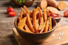 Bowl with sweet potato fries on table. Bowl with sweet potato fries on wooden table royalty free stock photos