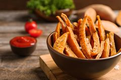 Bowl with sweet potato fries on wooden table. Space for text stock image