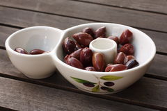 Bowl of tasty kalamata olives. On wooden table royalty free stock images