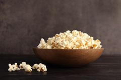 Bowl of tasty popcorn. On wooden table Royalty Free Stock Photography