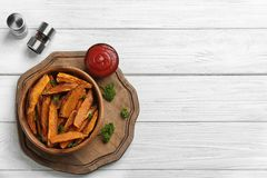 Bowl with tasty sweet potato fries on wooden background. Top view. Space for text royalty free stock photos