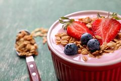 Bowl with tasty yogurt, berries and granola on table. Closeup Royalty Free Stock Image