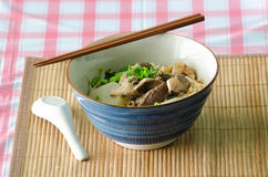 A bowl of Thai style beef noodle with spoon and chopstick. Royalty Free Stock Photography