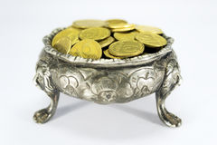 Bowl on three lions feet with coins. On green cloth Stock Photography