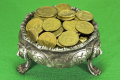 Bowl on three lions feet with coins. On green cloth Royalty Free Stock Photography