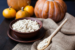 Bowl with toasted pumpkin seeds and wooden spoon Royalty Free Stock Image