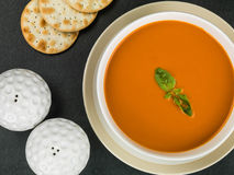 Bowl of Tomato and Basil Soup With water Biscuit Crackers and Salt and Pepper Royalty Free Stock Images