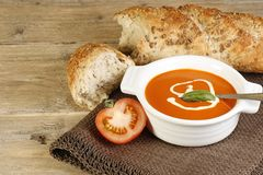 Bowl of tomato soup. Bowl of hot tomato soup and crusty bread on a wooden table Royalty Free Stock Photo