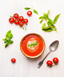 Bowl of tomato soup or gazpacho with spoon and basil on white wooden background Royalty Free Stock Images