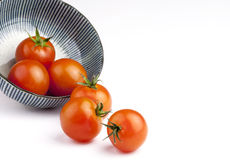 Bowl of tomatoes. Half empty bowl of tomatoes isolated on white background with copy space Royalty Free Stock Photos