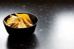 Bowl of tortilla chips. On a black kitchen counter Royalty Free Stock Image