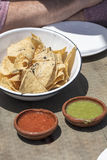 Bowl of tortilla chips with green and red salsa on a table. Bowl of corn tortilla chips with green and red salsa on a wood table Stock Image