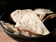 A bowl of tortilla chips. A bowl of tortilla chips side lit by the setting sun Royalty Free Stock Image