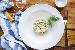 Bowl of traditional russian salad on wooden table Royalty Free Stock Photos