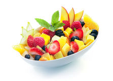 Bowl of tropical fruit salad. Bowl of colourful exotic tropical fruit salad with a sprig of fresh mint on a white background Stock Image