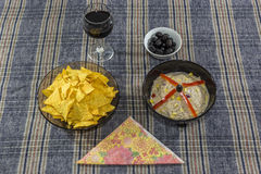 Bowl of tuna salad, tortilla chips, olives and glass of red wine Royalty Free Stock Image