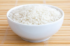 Bowl of uncooked white long grain rice on a bamboo mat Stock Photo
