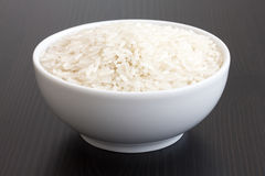 Bowl of uncooked white long grain rice on dark table Stock Image