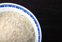 Bowl of uncooked white rice on wooden background. Royalty Free Stock Photography