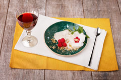 A bowl of vanilla ice cream with spices and raspberry. A glass of wine and ice cream with flower on a wooden background. Royalty Free Stock Photography