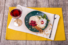 A bowl of vanilla ice cream with spices and raspberry. A glass of wine and ice cream with flower on a wooden background. Stock Photos