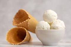 Bowl of vanilla ice cream and waffle cones on light background. Side view.  stock photography