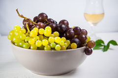 Bowl of various grapes: red, white and black berries on the white wooden table with glass of white wine and green leaf in the back. Ground . Selective focus Royalty Free Stock Photo