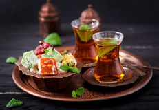 Bowl with various pieces of turkish delight lokum and black tea Royalty Free Stock Photo