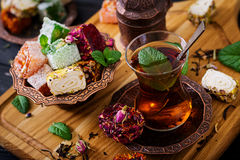 Bowl with various pieces of turkish delight lokum and black tea. With mint on a dark background royalty free stock photos