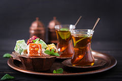 Bowl with various pieces of turkish delight lokum and black tea Royalty Free Stock Photography