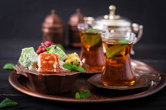 Bowl with various pieces of turkish delight lokum and black tea. With mint on a dark background royalty free stock images