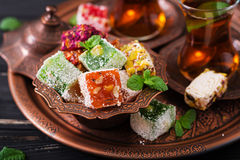 Bowl with various pieces of turkish delight lokum and black tea Stock Photo