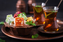 Bowl with various pieces of turkish delight lokum and black tea Stock Photography