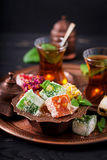 Bowl with various pieces of turkish delight lokum and black tea Royalty Free Stock Image