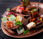Bowl with various pieces of turkish delight lokum and black tea Stock Images