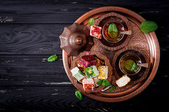 Bowl with various pieces of turkish delight lokum and black tea Royalty Free Stock Images