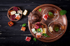 Bowl with various pieces of turkish delight lokum and black tea with mint Stock Image