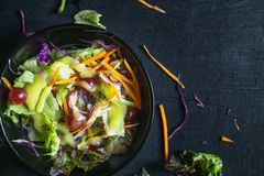 Bowl of vegetable salad on black background. royalty free stock photography