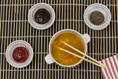 Bowl of vegetable soup with chopsticks on a bamboo serving mat Royalty Free Stock Images