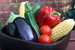 Bowl of Vegetables. Wooden bowl of summer vegetables on picnic table. Wall in background Stock Photos