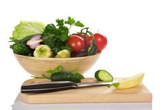 Bowl with vegetables, a chopping board and knife Royalty Free Stock Photos