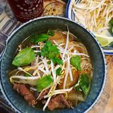 Bowl of Vietnamese pho. With fresh scallions, basil, bean sprouts, cilantro and beef Stock Image