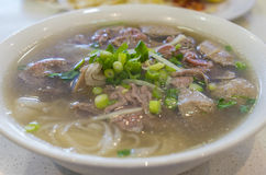 Bowl of Vietnamese pho noodle soup. With rare beef and beef ball served with onions and spring onions Stock Photo