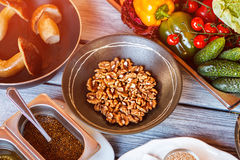 Bowl of walnuts beside mushrooms. Sauce container and vegetables. Grain mustard sauce. Create your own recipe Royalty Free Stock Image