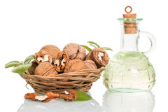 Bowl with walnuts and oil bottle isolated on white. Stock Photo